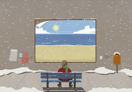 Man sitting on snowy bench looking at beach billboard