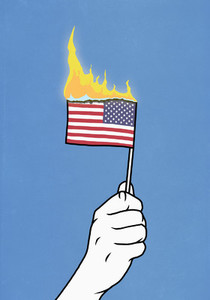 Hand holding burning American flag on blue background