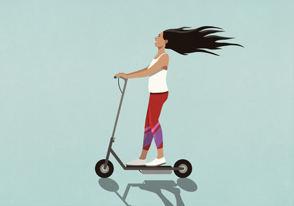Carefree young woman riding electric scooter