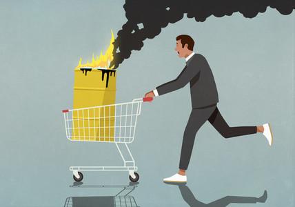 Businessman pushing shopping cart with burning oil barrel