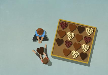 Man giving heart shape chocolate to woman