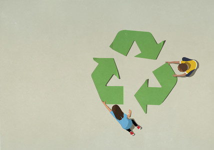 Boy and girl assembling green recycling symbol