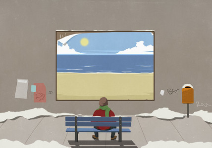 Man on urban winter bench looking at sunny beach billboard