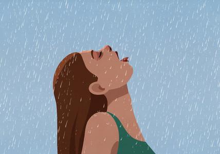 Woman with head back drinking falling rain