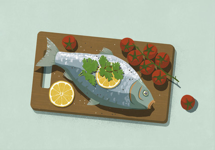 Whole cooked fish with lemons and tomatoes on cutting board