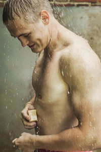 Young man with soap showering outdoors