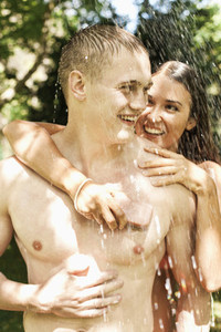 Happy young couple with soap showering outdoors