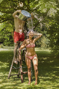 Playful boyfriend on ladder pouring water over girlfriend in bikini in summer backyard
