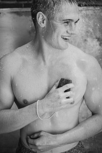 Happy young man with soap showering outdoors