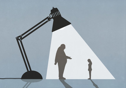 Boss towering over businesswoman under bright lamp