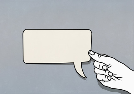 Hand holding speech bubble adhesive note