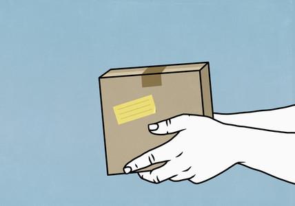 Hands holding cardboard box parcel