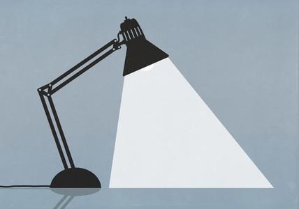 Bright task lamp shining on blue background