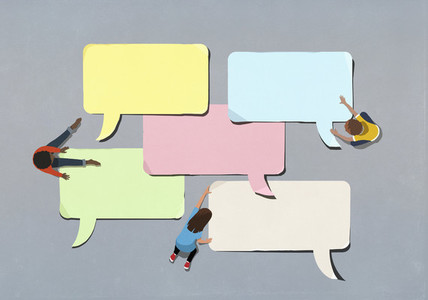 Kids arranging blank multicolor speech bubbles