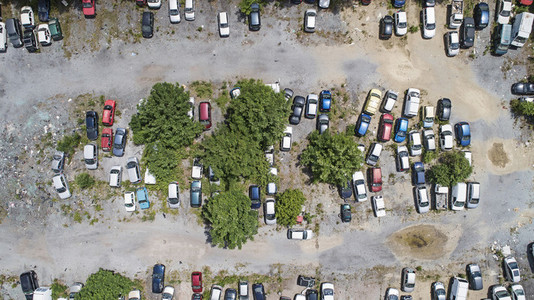 View from above cars parked among trees in parking lot