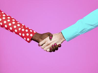 Multiethnic handshake on pink background