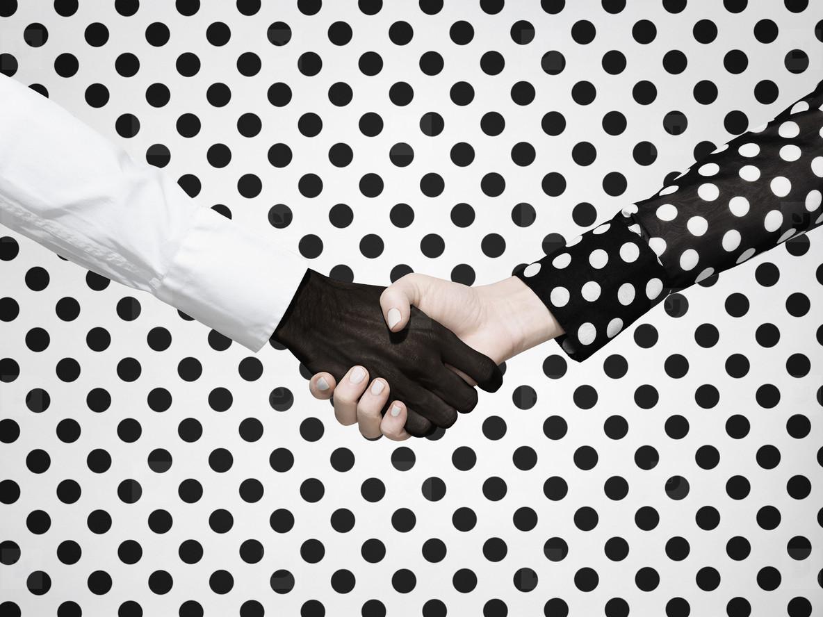 Multiethnic handshake on polka dot background