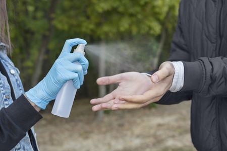 Close up woman in protective gloves spraying boyfriend with hand sanitizer