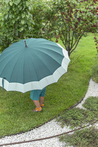 Toddler under large green umbrella in garden
