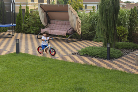 Carefree toddler boy riding bicycle in backyard