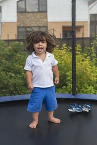 Portrait happy with cute toddler boy on backyard trampoline