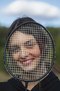 Portrait happy young woman behind badminton racket