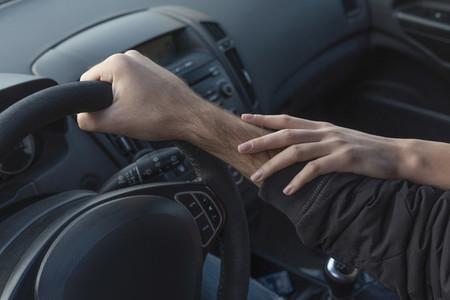 Woman touching arm of boyfriend driving car