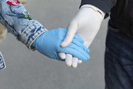 Close up affectionate couple holding hands in rubber gloves