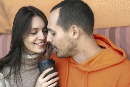 Romantic young couple sharing coffee with straws