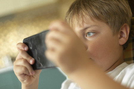 Close up focused boy playing video game on smart phone