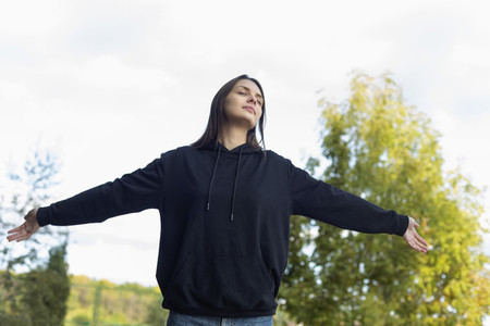 Carefree with serene young woman with arms outstretched