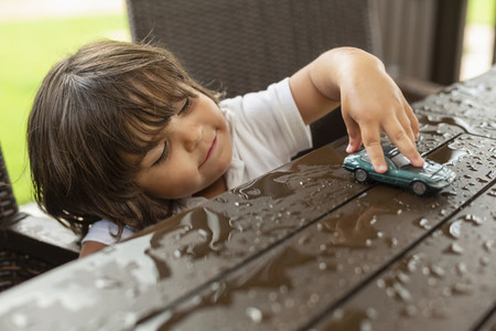 Cute toddler boy playing with toy car on wet patio table