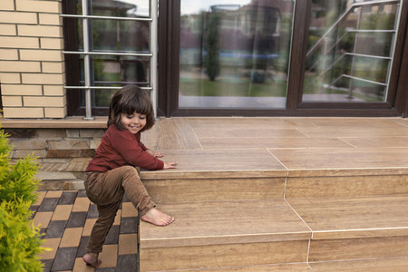 Cute barefoot toddler boy climbing patio steps