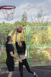 Young couple playing basketball at park basketball court