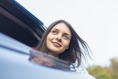 Portrait happy with carefree young woman leaning out car window