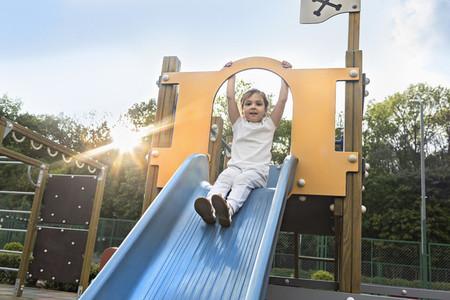 Portrait carefree girl on sunny playground slide