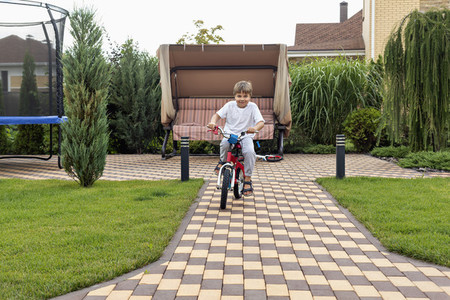 Portrait happy boy riding bicycle in backyard