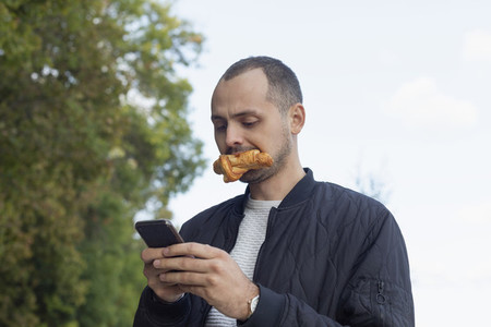 Young man eating and using smart phone