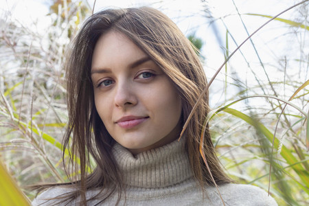 Close up portrait beautiful young brunette woman in tall grass