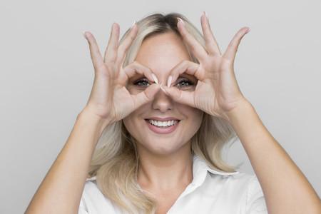 Portrait playful woman gesturing finger goggles