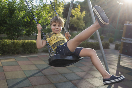 Portrait carefree boy swinging at sunny park playground