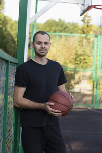 Portrait confident young man playing basketball at park basketball court