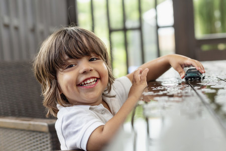 Portrait happy with cute toddler boy playing with toy car on wet patio table