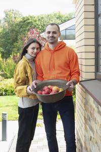 Portrait happy young couple with bowl of fresh harvested apples
