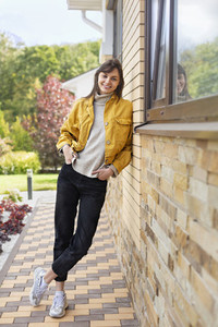 Portrait happy young woman in yellow jacket outside house