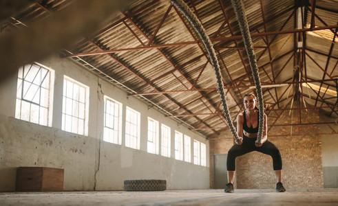 Woman exercising battling ropes at cross training gym
