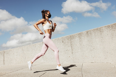 Sports woman wearing face mask running outdoors