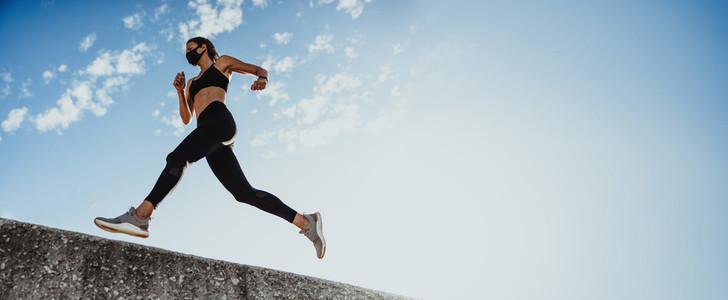 Panoramic shot of sportswoman running over wall
