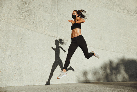 Athletic woman with face mask sprinting outdoors