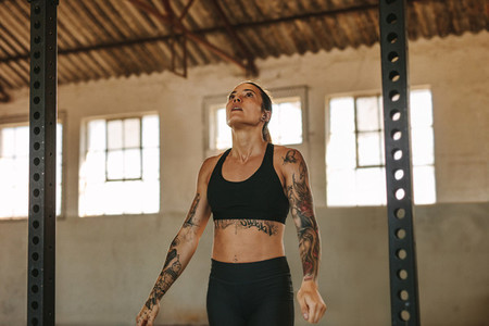 Tattooed woman exercising in an empty warehouse